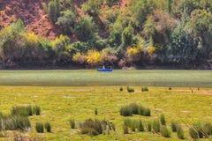 Een kleine vissersboot die zich op een rivier bewegen Royalty-vrije Stock Afbeelding
