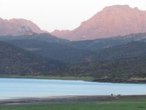 Een kleine vissersboot op een dam met bergen op de achtergrond Royalty-vrije Stock Foto's
