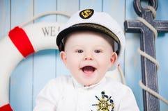 Een kleine vrolijke kapitein in een maritiem binnenland stock foto