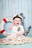 Een kleine vrolijke kapitein in een maritiem binnenland royalty-vrije stock foto's