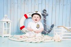 Een kleine vrolijke kapitein in een maritiem binnenland stock afbeeldingen