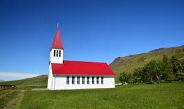 Een kleine witte kerk in IJsland met een rood dak stock foto