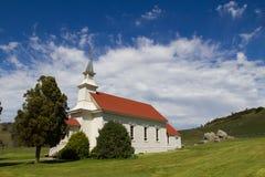 Zij hoek van een weinig witte kerk met een rood dak in Noordelijk Californië met fragmentarische blauwe hemelen Royalty-vrije Stock Fotografie