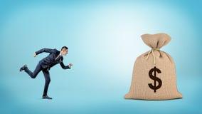 Een kleine zakenman die aan een reuze gesloten zak met een dollarteken lopen op het Royalty-vrije Stock Foto's