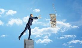 Een kleine zakenman die zich op een concrete kolom bevinden die en een dollarrekening vangen op een metaalhaak wordt gevangen stock fotografie