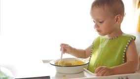 Een kleine zitting van de babyjongen als voorzitter en eet zelf havermoutpap op witte achtergrond stock footage