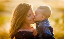 Een kleine zoon kust zijn moeder op het gebied Royalty-vrije Stock Afbeelding