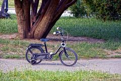 Een kleine zwarte fiets op de stoep in het park Stock Foto