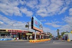 Een kleinere weg die Koningenweg uitzetten bij Tavua-stad, Fiji met kleinhandelswinkels en een groot aanplakbord Stock Afbeelding