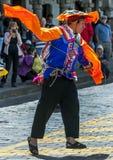 Een kleurrijk geklede mens presteert onderaan een Cusco-straat tijdens de Meidagparade in Peru royalty-vrije stock foto's