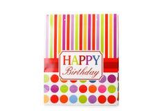 Een kleurrijk pakket met rode, gele en roze strepen en een zin gelukkige die verjaardag op een witte achtergrond wordt geïsoleerd Stock Foto's