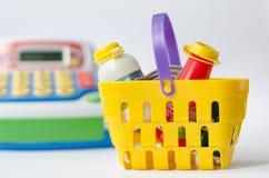 Een kleurrijke die stuk speelgoed het winkelen mand met kruidenierswinkels wordt gevuld stock afbeeldingen