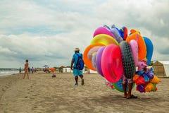Een kleurrijke floaterverkoper die op een strand lopen royalty-vrije stock fotografie