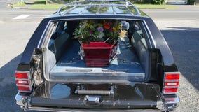 Een kleurrijke kist in een lijkwagen of een kapel vóór begrafenis of begrafenis bij begraafplaats stock afbeeldingen