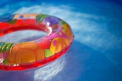 Een kleurrijke ring die in een verfrissend blauw zwembad drijven stock afbeeldingen
