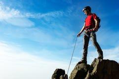 Een klimmer helpt zijn partner om de top van bergpe te bereiken stock afbeelding