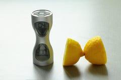 Een klok en twee stukken van een citroen op de lijst Stock Fotografie