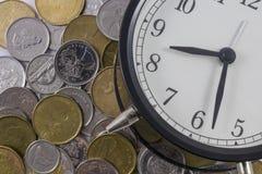 Een klok op een stapel van verandering Stock Foto