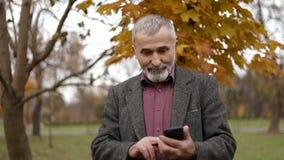 Een knap bejaarde die glazen dragen en een telefoon met behulp van Gang in het park in de Herfst stock footage