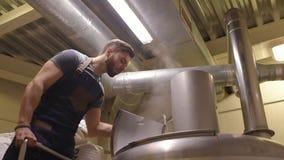 Een knap gebaard mannelijk gegeven van brouwersverslagen tegen een achtergrond van biertanks stock video