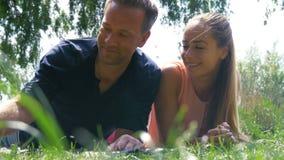 Een knap paar die in het park koelen - Blazende paardebloem stock video