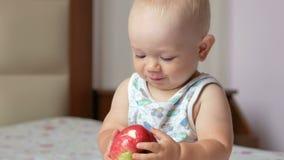 Een knappe baby eet een appel in bed bij ontbijt hij een stuk afbijt en zijn mond aanbrengt stock videobeelden