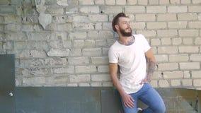 Een knappe brutale mens met een baard in jeans en een witte T-shirt op de achtergrond van een grijze bakstenen muur en een bouw stock footage