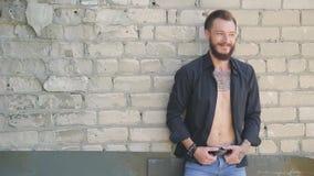 Een knappe brutale mens met een baard in jeans en een zwart overhemd op de achtergrond van een grijze bakstenen muur stock footage
