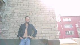 Een knappe brutale mens met een baard in jeans en een zwarte T-shirt op de achtergrond van een grijze bakstenen muur stock video