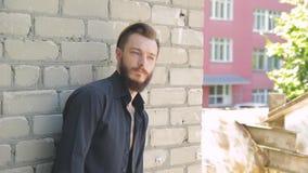 Een knappe brutale mens met een baard in jeans en een zwarte T-shirt op de achtergrond van een grijze bakstenen muur stock videobeelden
