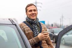 Een knappe jonge mens bevindt zich naast een auto die en het drinken koffie glimlachen stock foto