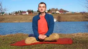 Een knappe jonge mens die yoga op een pier met tropische eilandachtergrond doen stock video