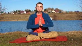 Een knappe jonge mens die yoga op een pier met tropische eilandachtergrond doen stock videobeelden