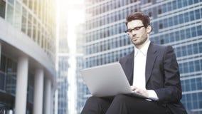 Een knappe jonge zakenman die met laptop in bedrijfsdistrict werken Royalty-vrije Stock Afbeeldingen