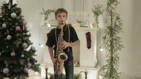 Een knappe jongen speelt de saxofoon op de achtergrond van de Kerstboom Het overleg van het vakantiehuis stock videobeelden
