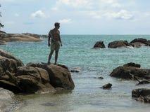 Een knappe kerel in een overhemd wordt uitgerekt op een rots en kijkt weg Exotische overzeese mening Wild strand met grote stenen royalty-vrije stock foto's