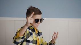 Een knappe kerel in zonnebril luistert aan muziek van de telefoon in witte hoofdtelefoons en hij pret dansend in het wit stock videobeelden