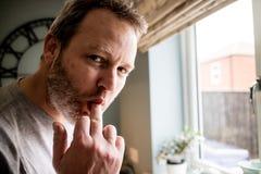 Een knappe mens die een dwaas gezicht met zijn vinger in zijn mout trekken stock foto