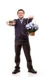 Een knappe mens in een kostuum en glazen, met snoepjes en bloemen; W stock fotografie