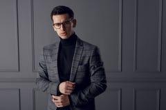 Een knappe mens in een grijs jasje en zwarte zich vooraan bevinden en col die, die zeker, op grijze muurachtergrond kijken stock afbeeldingen