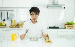 Een knappe mens heeft ontbijt in de moderne keuken royalty-vrije stock foto's