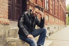 Een knappe mens met baardzitting op stappen buiten het dragen van een je Royalty-vrije Stock Foto