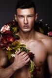 Een knappe mens met een naakte torso, bronstan en bloemen op zijn lichaam stock fotografie