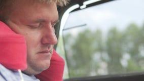 Een knappe mens slaapt in een auto op een reizend hoofdkussen stock footage