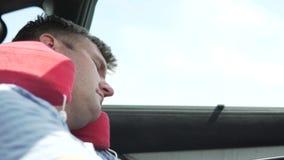 Een knappe mens slaapt in een auto op een reizend hoofdkussen stock video