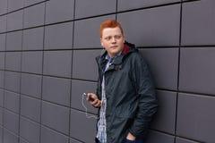 Een knappe roodharigejongen met sproeten die zwart jasje, gecontroleerde overhemd en jeans dragen die zich tegen zwarte smartphon royalty-vrije stock fotografie