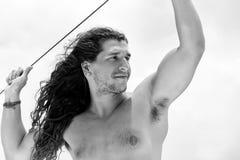 Een knappe sportieve sexy kerel met lang haar tegen witte achtergrond Reis op een jacht door overzees Reisbeeld Het concept van d stock afbeeldingen