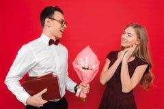 Een knappe student, die glazen dragen, geeft een gift en een boeket van bloemen aan zijn meisje tegen een rode achtergrond royalty-vrije stock foto's