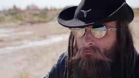 Een koele cowboy in een zwarte hoed en glazen met een baard onderzoekt de afstand in de woestijn stock video