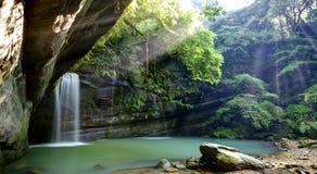 Een koele verfrissende waterval in een smaragdgroene die vijver in een geheimzinnig bos van het weelderige Landschap van de groen Royalty-vrije Stock Foto